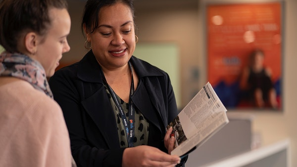 Woman showing another woman information booklet.