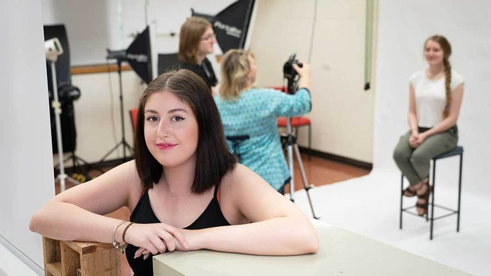 GOTAFE Graphic Design student squating down with a photoshoot going on in the background