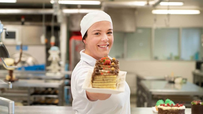 GOTAFE Baking Student holding a baked cake standing side on
