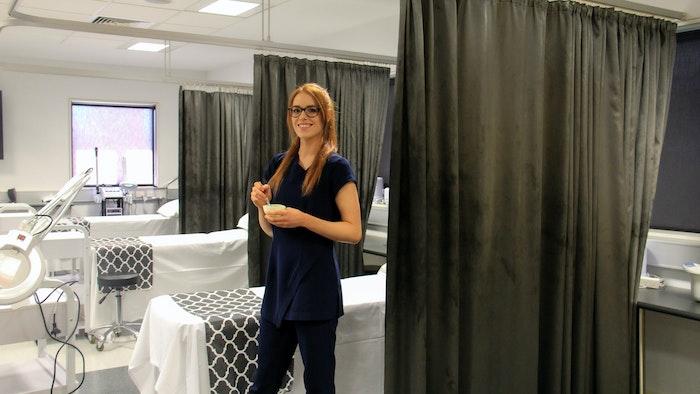 Laura Zapasnik standing in salon class room