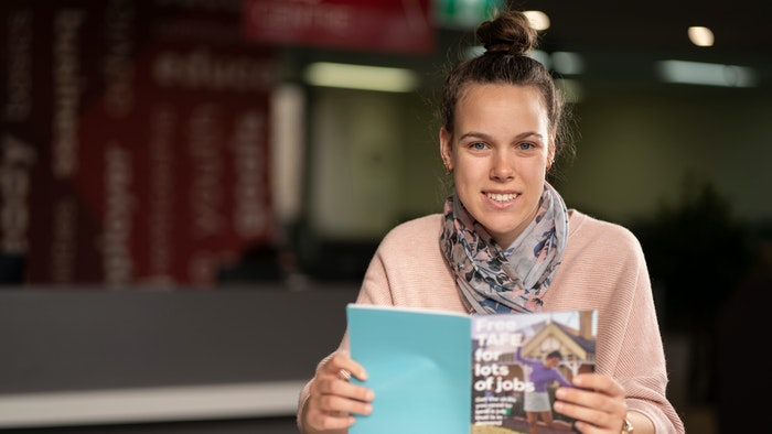 Student sitting reading Free TAFE book