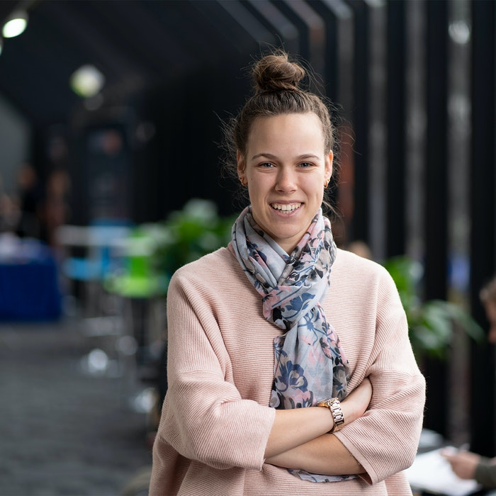 Woman smiling with arms crossed in GOTAFE foyer
